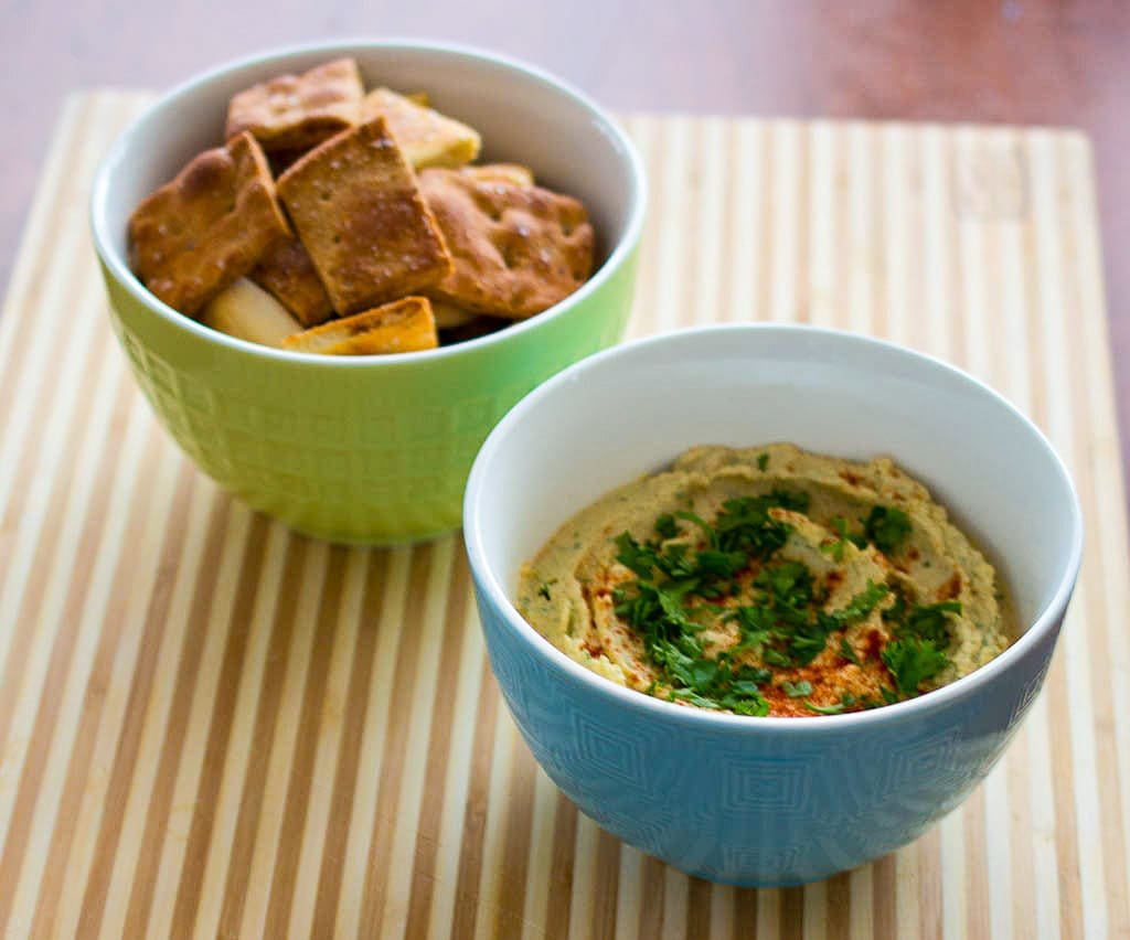 Roasted garlic hummus with black pepper pita chips is made with traditional Middle Eastern ingredients.