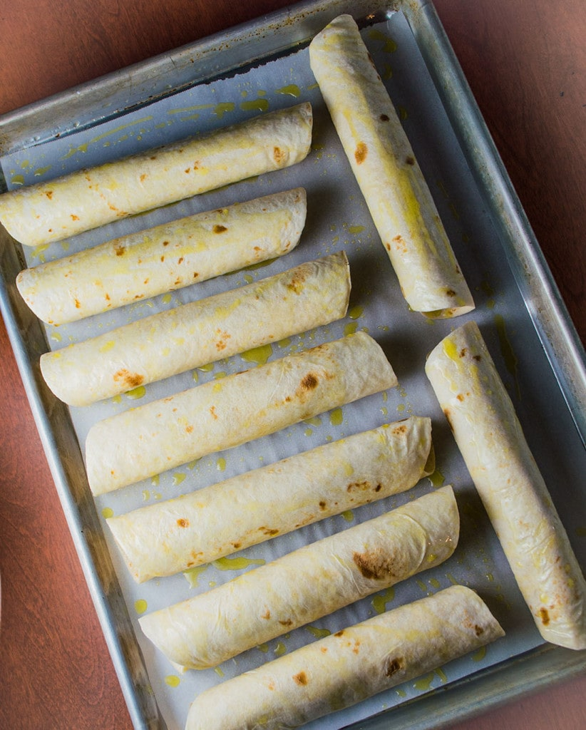 Rolled green chile chicken taquitos are ready to go into the oven.