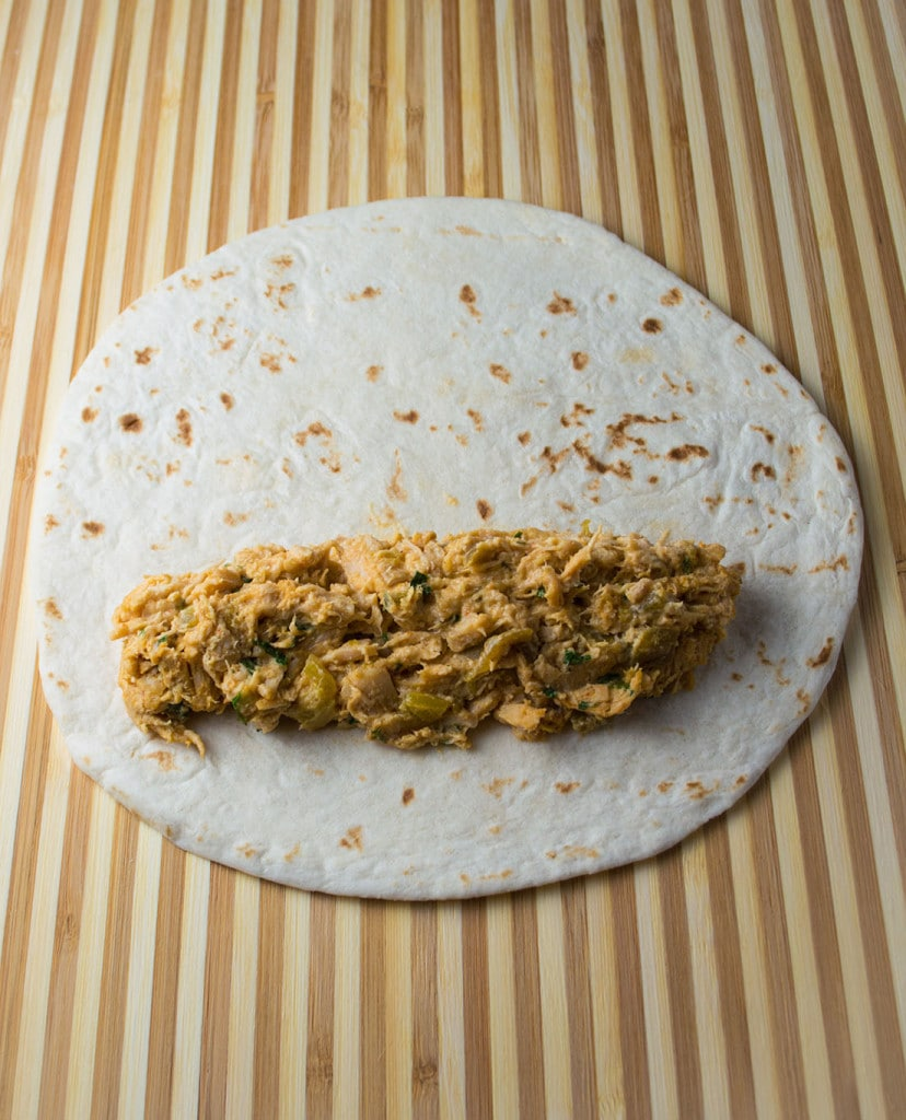 A creamy green chile chicken filling is rolled into flour tortillas for baked taquitos.