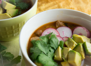 This easy red posole for the pressure cooker or crock pot is topped with cilantro, avocado and sliced radishes.