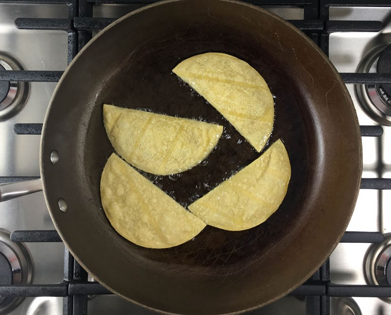 Corn tortillas are crisped in a frying pan for bean and chorizo tostadas.