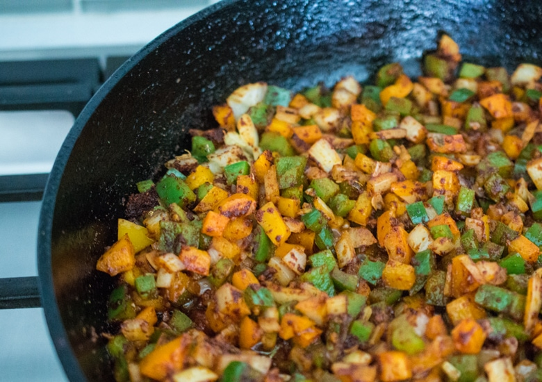 Fresh peppers, onions, garlic, and warm, aromatic spices sauté in a skillet for Instant Pot beef chili.