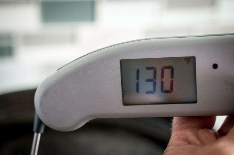 Food thermometer showing the correct temperature for medium rare steak, 130 degrees Fahrenheit