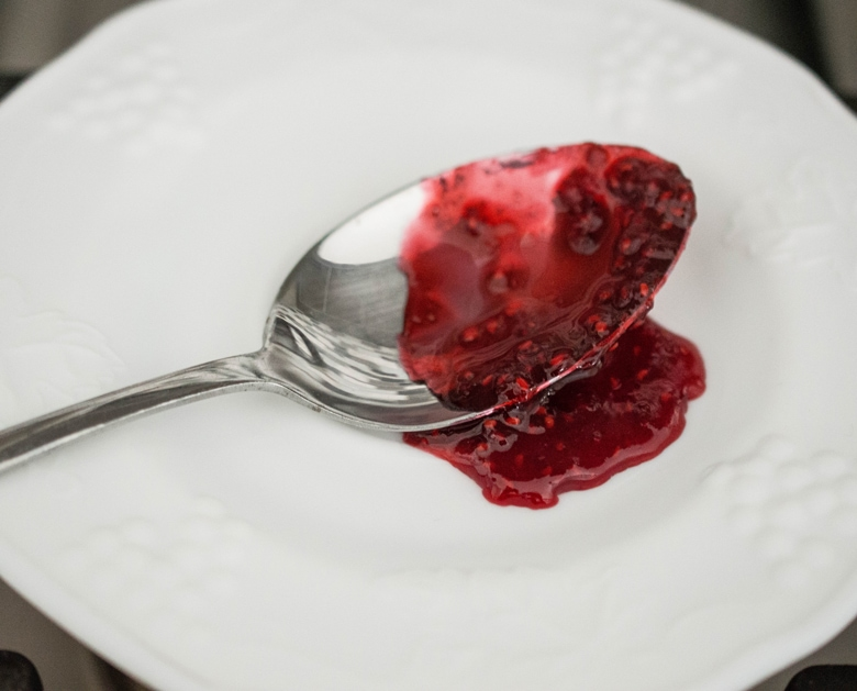Pour homemade low sugar raspberry jam on a cold plate to check the texture.