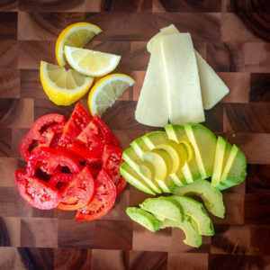 Avocado, Monterey Jack cheese, lemon and tomato on a cutting board