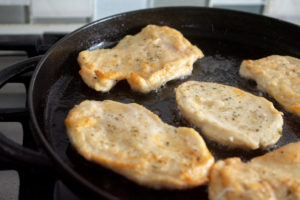 chicken cutlets cooking in skillet