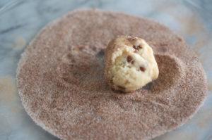 cinnamon chip snickerdoodle dough being rolled in cinnamon sugar