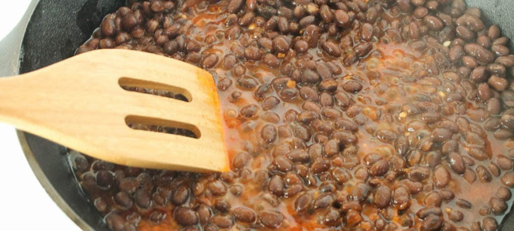 best ever mexican black beans in a skillet with a wooden spoon