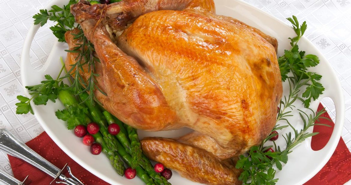 roast turkey on a platter garnished with herbs, cranberries and asparagus