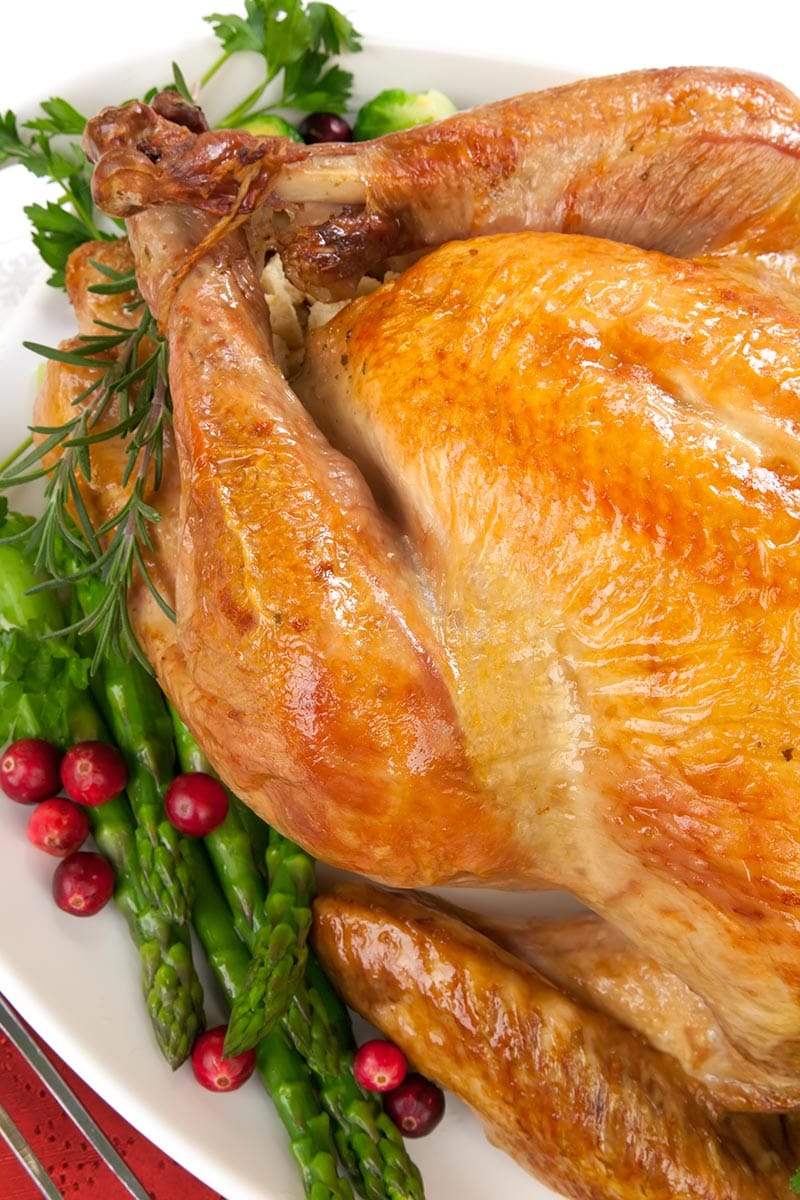 Roast turkey on a platter with cranberries, herbs, and asparagus