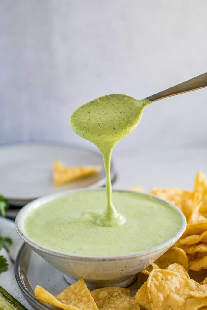 Creamy Jalapeno Sauce in a bowl with spoon surrounded by chips