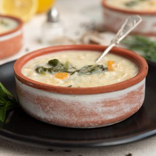 lemon chicken orzo soup in a ceramic bowl on a black plate with a silver spoon