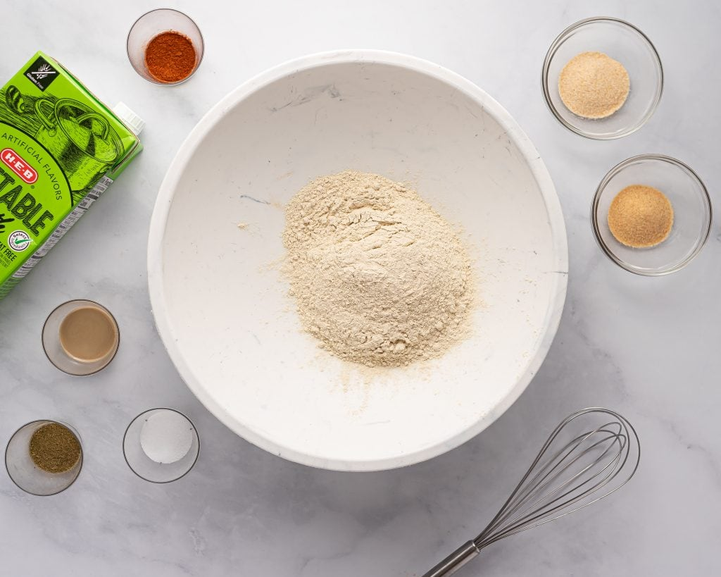 ingredients for making homemade seitan with vital wheat gluten, garlic and onion powders, paprika, vegetable broth and tahini