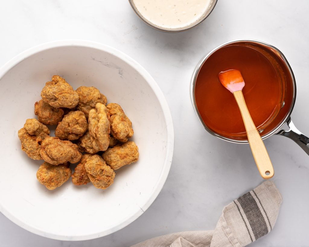 Deep fried seitan wings in a bowl with buffalo sauce and blue cheese dip