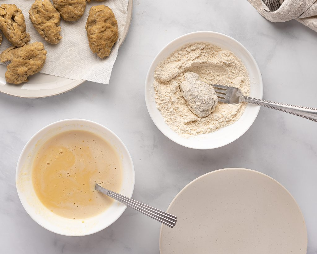 coating a cooked seitan wing in seasoned flour to coat