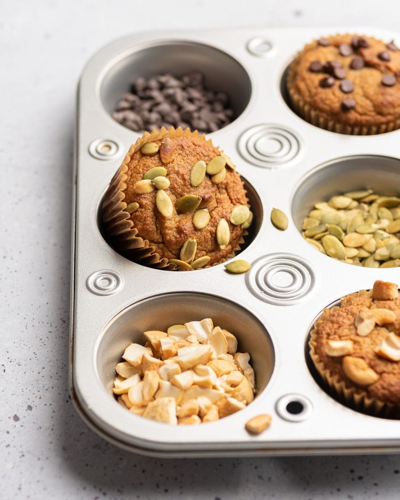 muffin tin with almond flour banana muffin topped with pumpkin seeds
