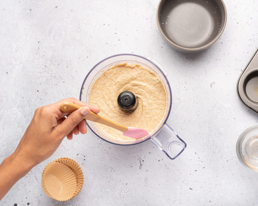 scraping down the sides of a food processor with muffin batter inside with a spatula