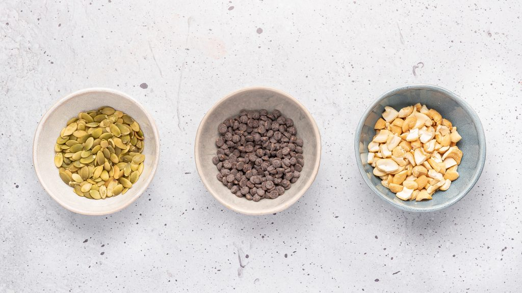 three small bowls with chocolate chips, chopped cashews and pumpkin seeds