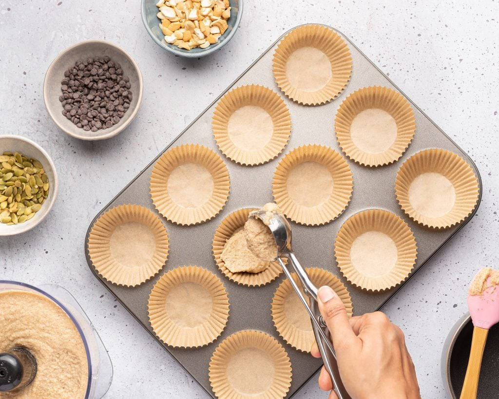 filling a muffin tin with almond flour banana batter