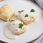 white plate with a vegan biscuit covered in white gravy