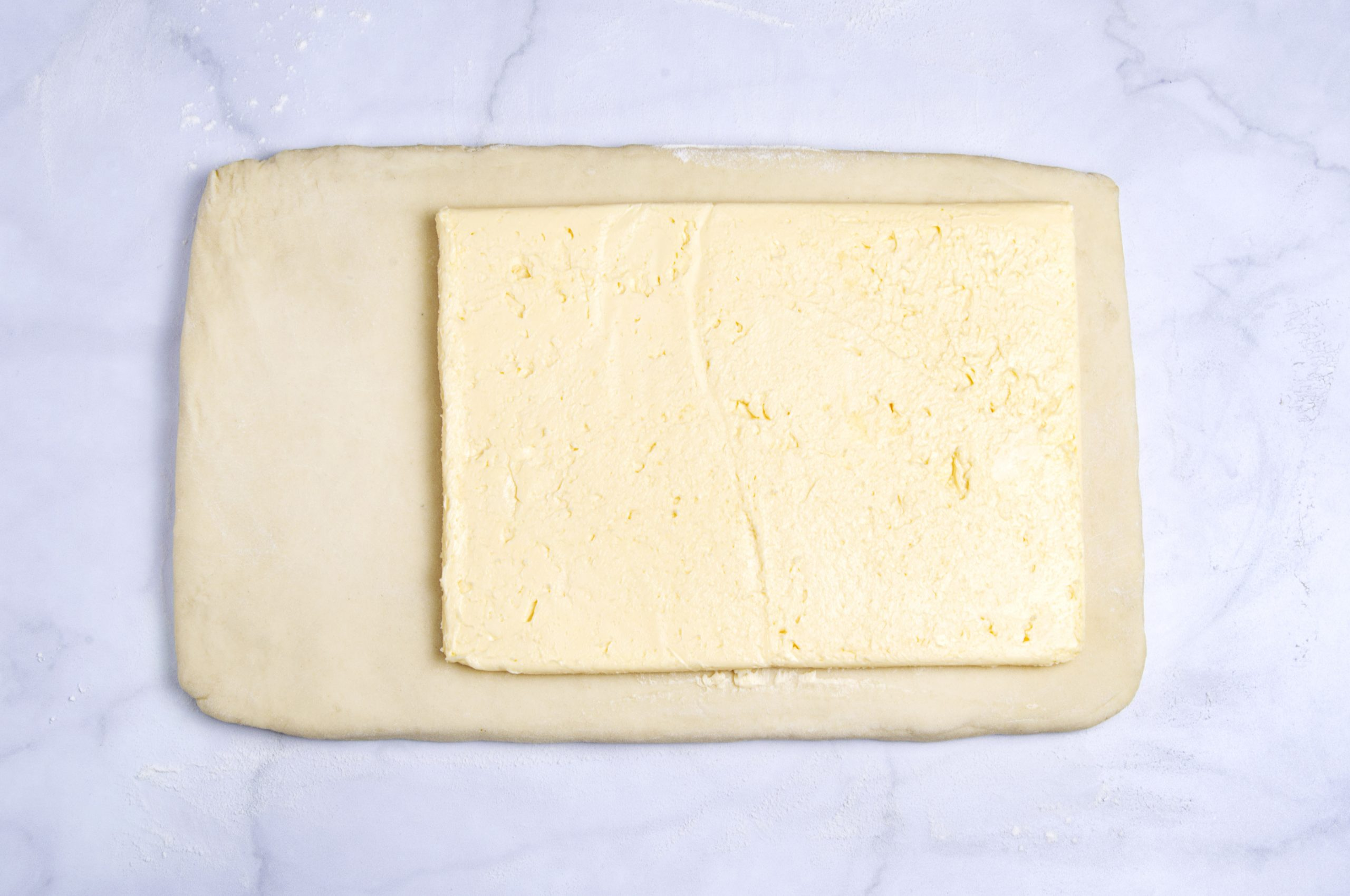 rectangle of croissant dough with a block of butter on top