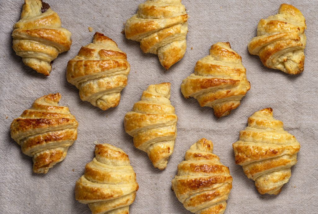baked golden plant-based croissants on a baking sheet with parchment paper