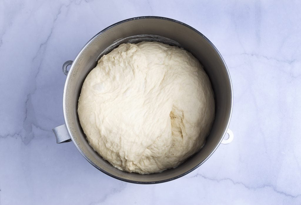 risen croissant dough in a mixing bowl