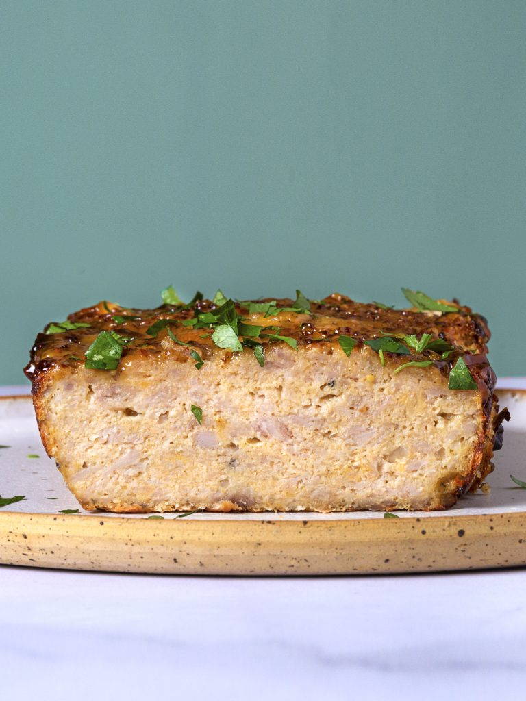 slices of chicken meatloaf on a wooden board with a green background