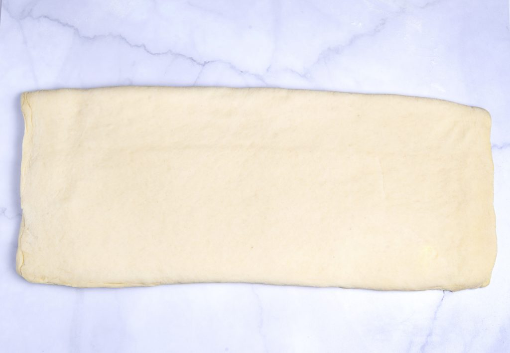 first step in folding vegan croissant dough on a marlbe board