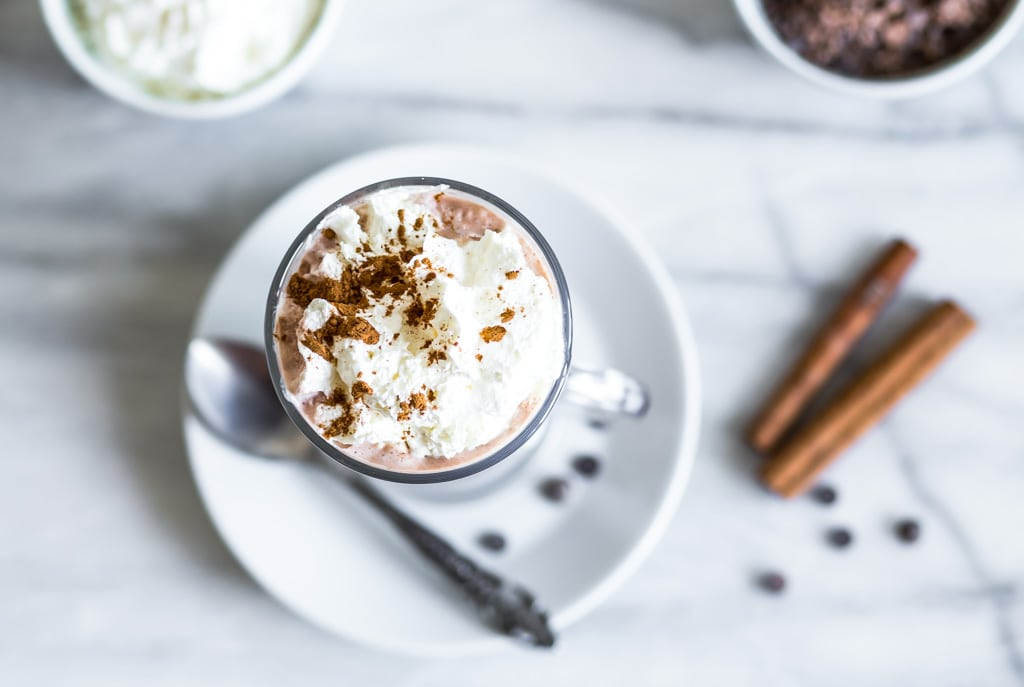 glass of plant-based hot chocolate with whipped cream and cinnamon on a white plate