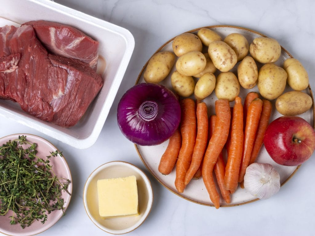 ingredients for pot roast: chuck roast, carrots, potatoes, purple onion and herbs