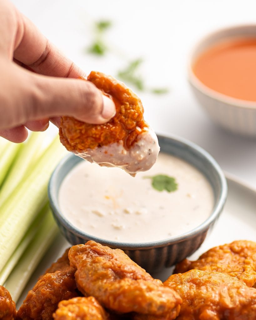dipping a crispy vegan buffalo wing in blue cheese dressing