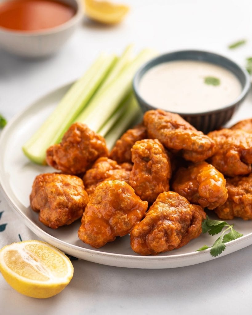 plate of vegan buffalo wings with blue cheese sauce and a fresh lime