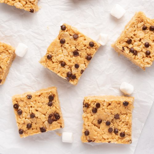peanut butter rice krispie treats with chocoalte chips on a piece of parchment paper