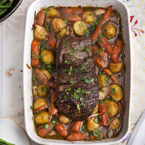 sous vide pot roast in a baking dish with vegetables and gravy