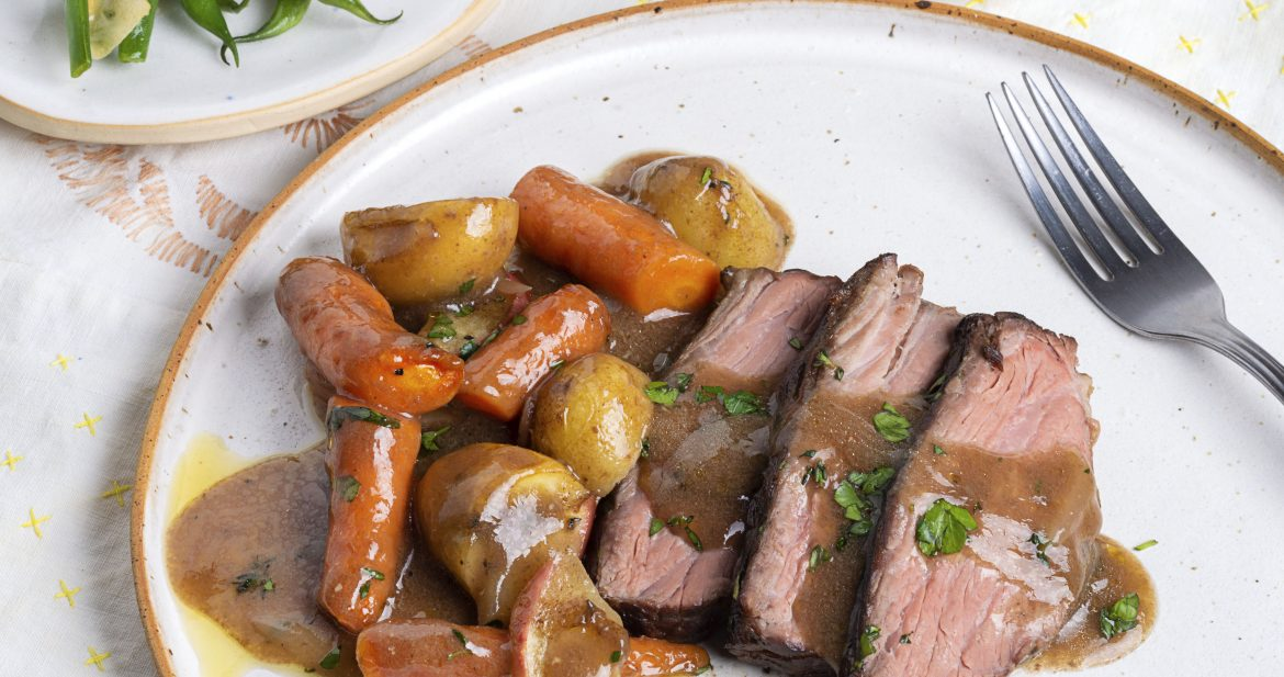 white plate of pot roast with gravy, potatoes and carrots