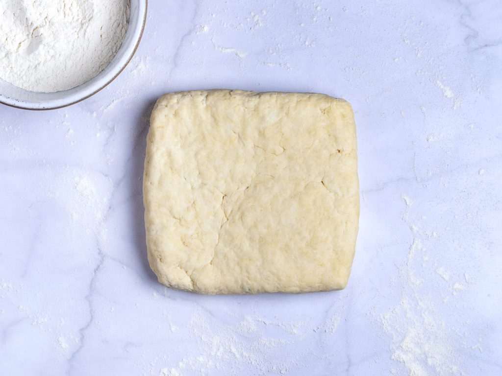 shaped biscuit dough in a square on a marble pastry board