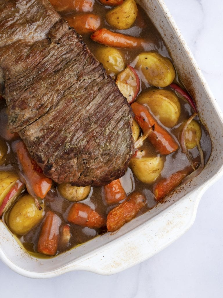 sous vide pot roast in a baking dish with gravy, carrots and potatoes