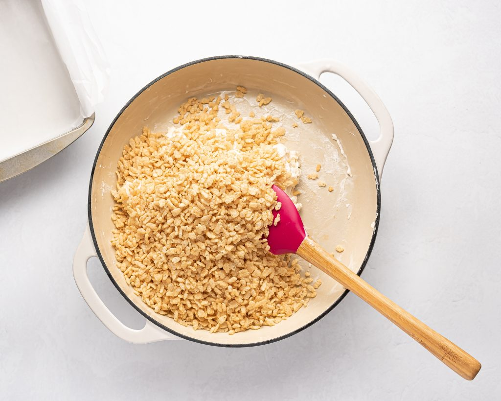 adding cereal to melted marshmallows and butter in a pot