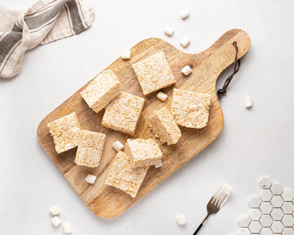 vegan rice krispie treats on a wooden cutting board