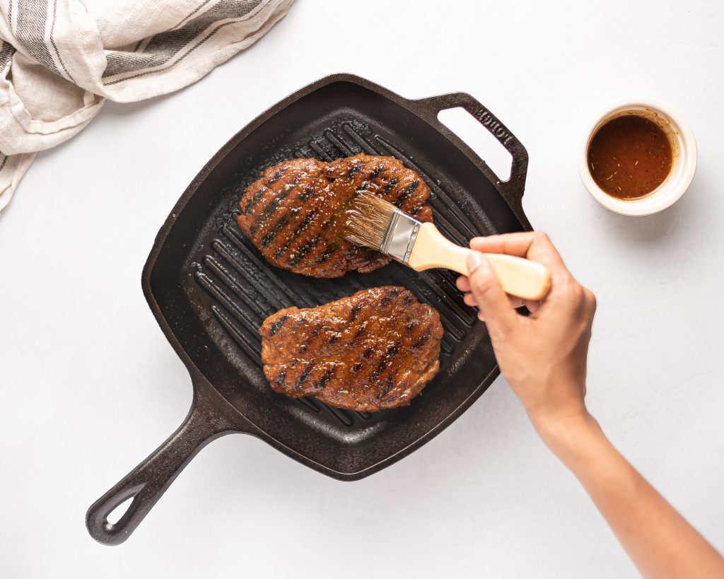 grilling vegan seitan steaks on an indoor grill pan with someone brushing marinade on top