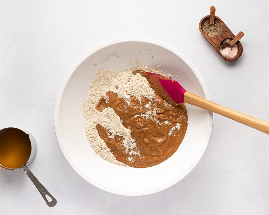 mixing vital wheat gluten into wet ingredients in a white bowl with a red spatula