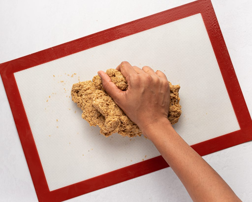 hand kneading vegan seitan dough on a silicone mat