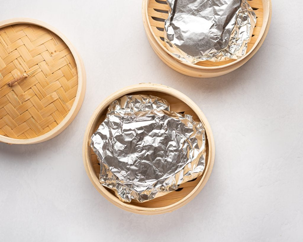 bamboo steamer basket with seitan steaks wrapped in aluminum foil