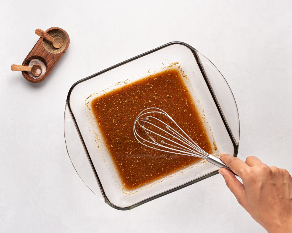 whisking steak marinade in a square bowl