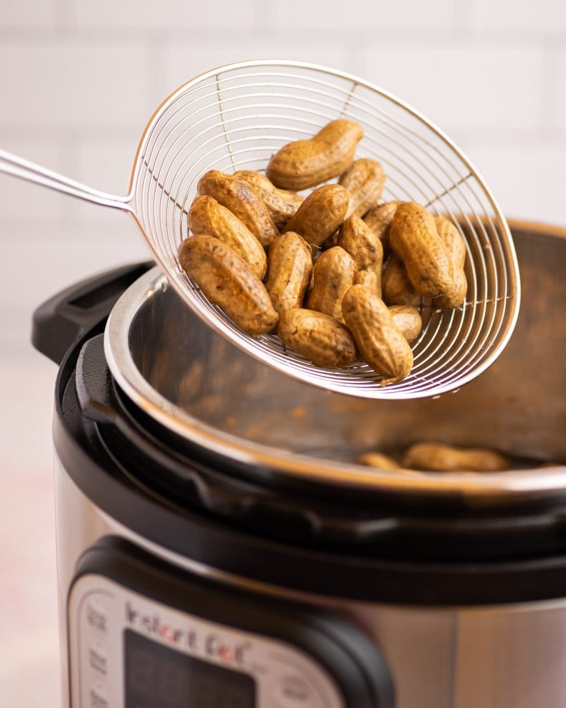 strainer removing boiled peanuts from an instant pot