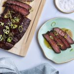 sous vide flank steak sliced on a wooden cutting board with sliced scallions