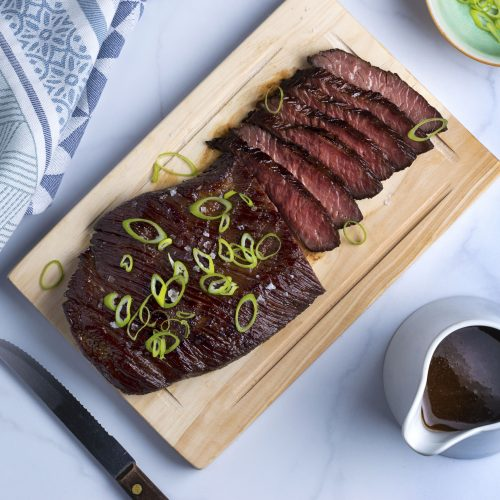 flank steak with scallions on a wooden cutting board