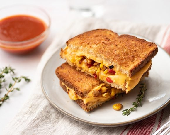 Healthy grilled cheese with veggies sliced in half on a white plate