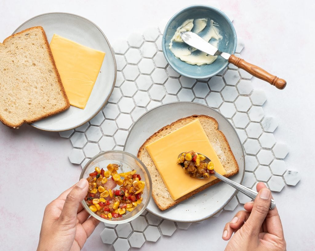 assembling a grilled cheese sandwich with cooked vegetables and cheddar cheese